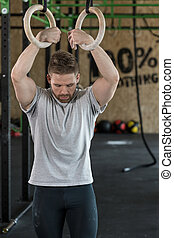 Strongman with gymnastic rings - Young attractive strongman...