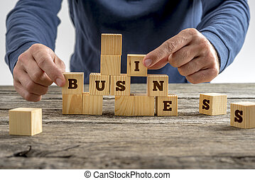Man building the word Business with blocks - Close up of the...