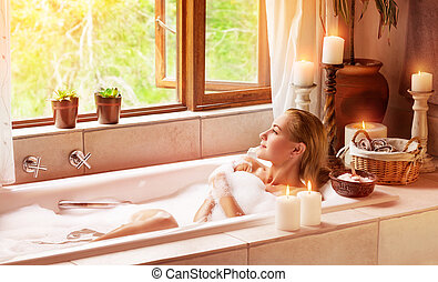 Woman bathing with pleasure, lying down in the tub with foam...