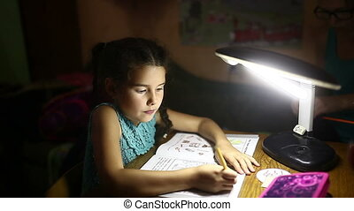teen in the evening doing girl homework lessons draws light...