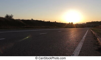 Young boy on his bike on the road in sunset