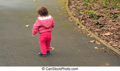 Child walks in the park alone - Toddler child girl age one...