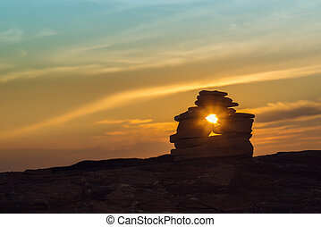 Close-up of Inukshuk stones on ocean shore at sunset Central...