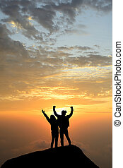 silhouette achievements successful arm up couple is on peak of hill celebrating success with sunrise