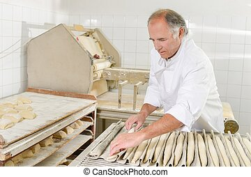 Baker preparing baguettes