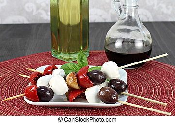 Antipasto skewers of red peppers, mozzarella, garlic and...