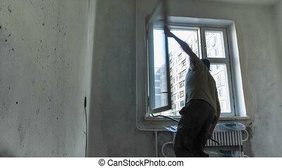 Installation of plastic windows - One worker takes in the...