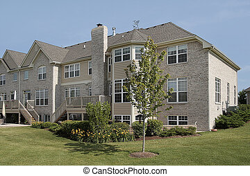 Three story suburban townhouse with balcony and landscaping
