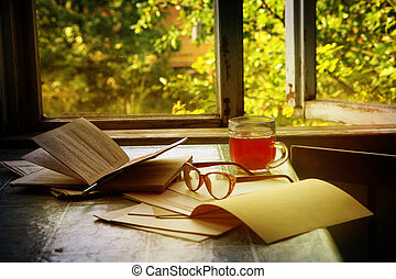 Still life with books, glasses and a compote on the table by the open window
