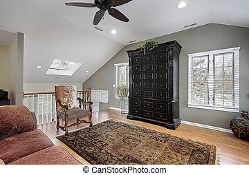 Second floor family room with staircase and skylight