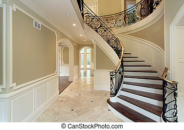 Foyer in new construction home with curved staircase