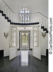 Traditional foyer with double entry door and staircase