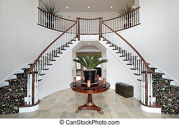 Modern foyer with double staircase and large circular table