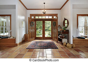 Foyer with orange ceramic floors - Foyer in modern home with...