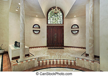 Marble foyer in luxury home with chandelier