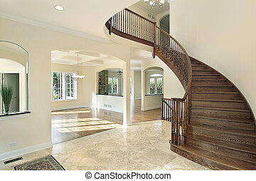 Foyer in new construction home with circular staircase