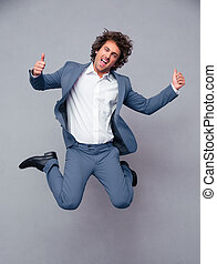 Businessman jumping and showing thumbs up - Portrait of a...