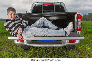 boy laying on car trunk on natural background