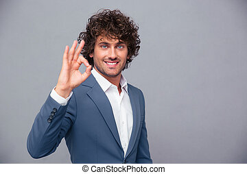 Smiling businessman showing ok sign - Portrait of a smiling...
