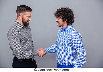 Portrait of a two casual men doing handshake over gray...