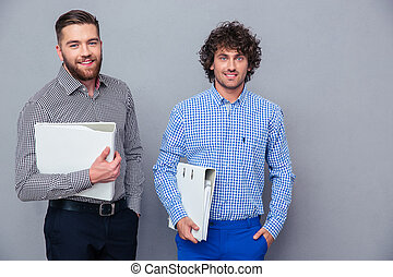Portrait of a two casual businessmen holding folders on gray...