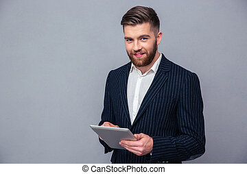 Happy businessman using tablet computer