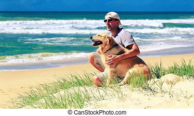 Male owner and dog on a beach - Male owner sitting on a...