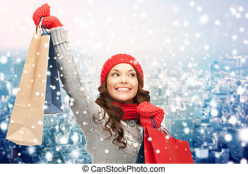 happy woman in winter clothes with shopping bags - holidays,...
