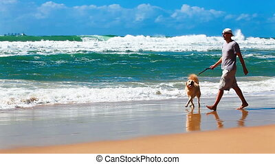 Male owner on a beach with a dog