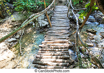 old wooden bridge through stream - small old wooden bridge...