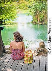 Travel woman enjoying beautiful lake Lonely young girl...