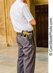 Security guard standing and armed with shackles, a gun and...