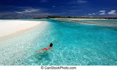 Young woman swimming in lagoon - Young woman swimming in...