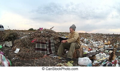 man unemployed homeless dirty looking food dump waste in landfill  social