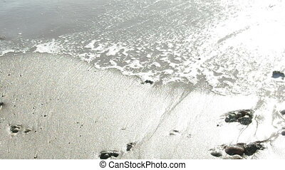 shoreline footsteps - ocean waves deleting footsteps on sand