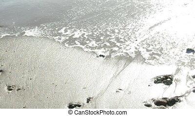 shoreline footsteps - ocean waves deleting footsteps on sand
