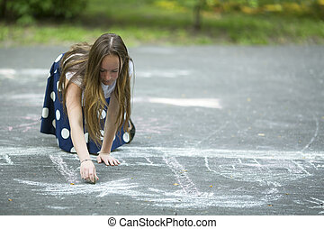 Teen girl drawing with chalk on the pavement