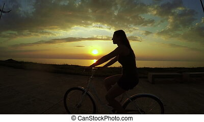 Girl on bicycle at sunset - Girl riding bike on seafront