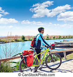 MTB Biker Bicycle touring on the river with pannier - MTB...