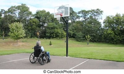 wheelchair basketball - A disabled man plays basketball from...