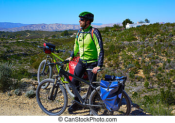 cycling tourist cyclist in Pedralba Valencia with paniers -...