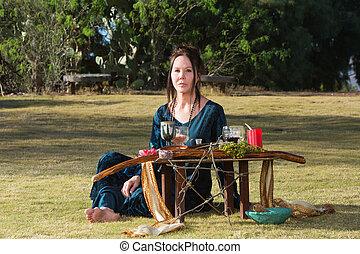 Serious Priestess with Pagan Altar - Serious priestess in...
