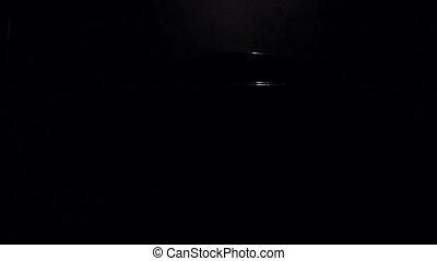 Car in the parking in dark garage, the door opens and...