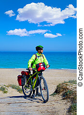 MTB Biker Bicycle touring on a beach with pannier - MTB...