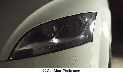 Close-up of headlights of white car in garage in the...