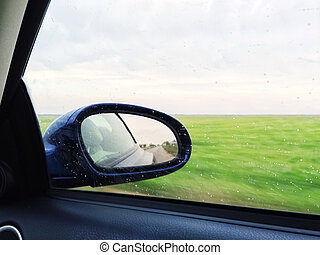 View over green fields from a modern car