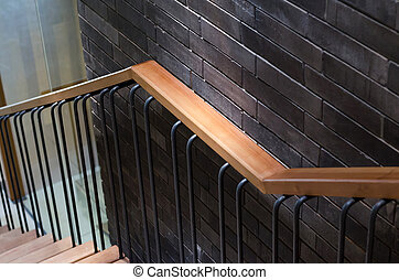 Wooden handrail with brick wall background