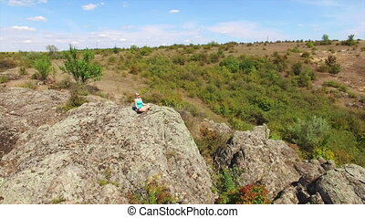 Aerial: Woman sitting on the rock