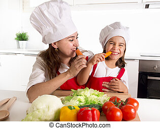 happy mother and little daughter in apron and cook hat...