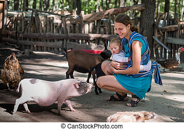 Happy mother and her daughter with baby goats on the...